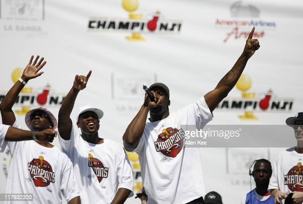 Gary Payton Dwyane Wade and Shaquille O'Neal of the Miami Heat celebrate during the victory parade and celebration at American Airlines Arena on June...