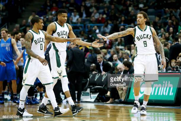 Gary Payton II Giannis Antetokounmpo and Michael Beasley of the Milwaukee Bucks walk across the court in the third quarter against the Dallas...