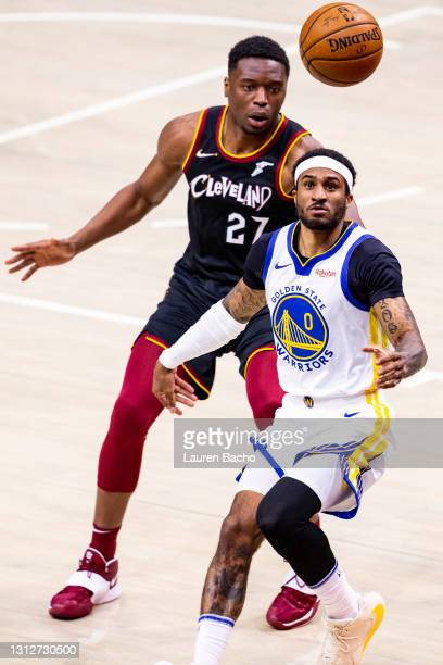 Gary Payton II of the Golden State Warriors and Mfiondu Kabengele of the Cleveland Cavaliers run after the ball during the fourth quarter at Rocket...