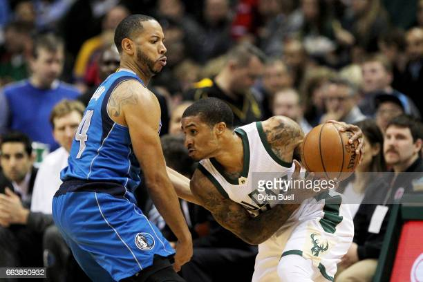 Gary Payton II of the Milwaukee Bucks handles the ball while being guarded by Devin Harris of the Dallas Mavericks in the third quarter at BMO Harris...