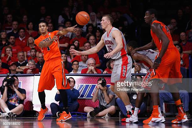 Gary Payton II of the Oregon State Beavers passes the ball around Kaleb Tarczewski during the college basketball game at McKale Center on January 30...