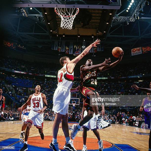 Gary Payton of the Eastern Conference shoots a layup against Christian Laettner of the Eastern Conference during the 1997 AllStar Game on February 9...