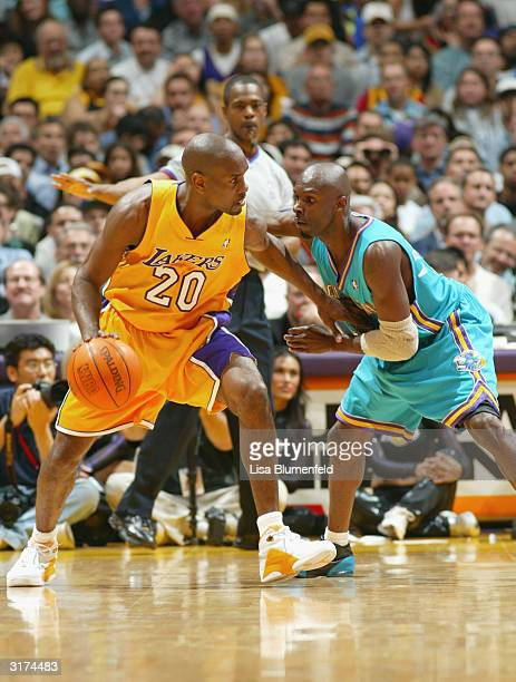 Gary Payton of the Los Angeles Lakers handles the ball under pressure from Darrell Armstrong of the New Orleans Hornets during a game March 30 2004...