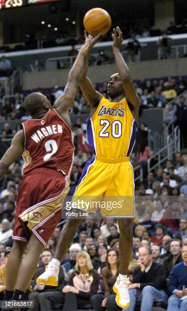 Gary Payton of the Los Angeles Lakers shoots over Dajuan Walker during the game between the Cleveland Cavaliers and the Los Angeles Lakers at the...