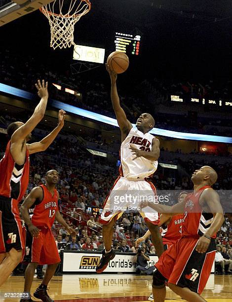 Gary Payton of the Miami Heat tries to score between Loren Woods and Darrick Martin of the Toronto Raptors on April 11 2006 at American Airlines...