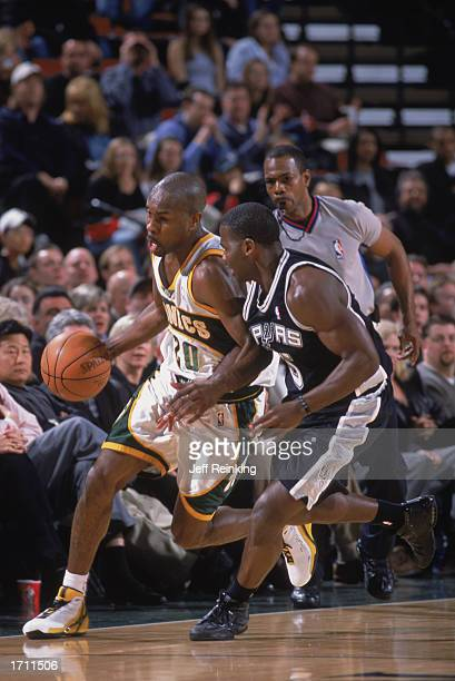 Gary Payton of the Seattle Sonics drives the ball against Anthony Goldwire of the San Antonio Spurs at Key Arena on December 18, 2002 in Seattle,...
