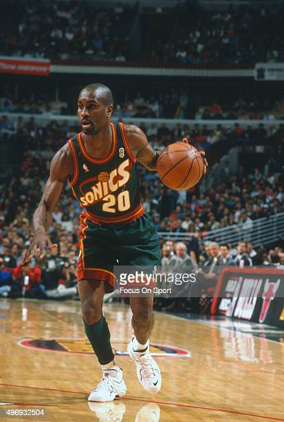 Gary Payton of the Seattle Supersonics dribbles the ball against the Chicago Bulls during an NBA basketball game circa 1995 at the United Center in...