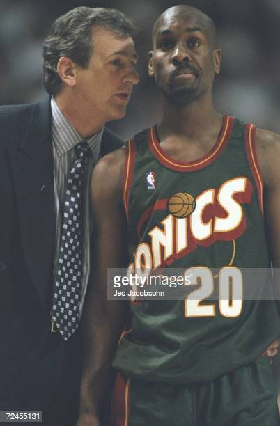 Gary Payton of the Seattle SuperSonics looking on while Head Coach Paul Westphal talks to him during the game against the Sacramento Kings at the...