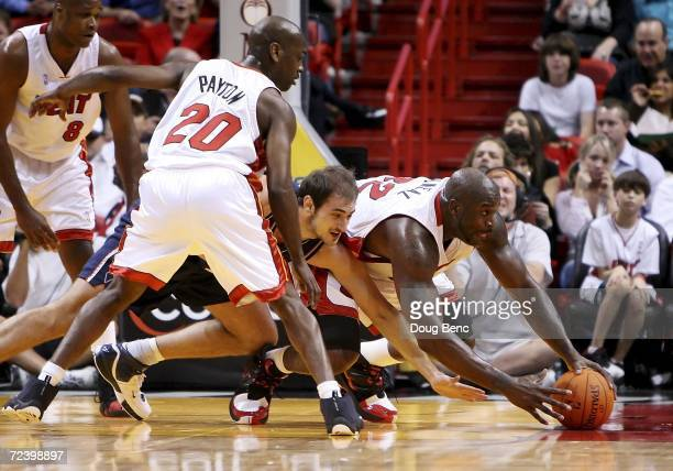 Gary Payton watches as Shaquille O'Neal of the Miami Heat battles for a loose ball with Nenad Krstic of the New Jersey Nets at American Airlines...