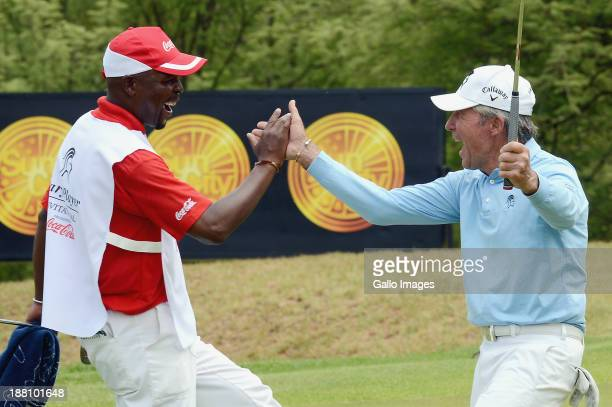 Gary Player celebrates sinking a putt with his caddie during the ProAm of the Gary Player Invitational presented by CocaCola at The Lost City Golf...