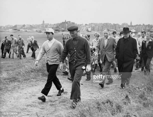Gary Player of South Africa and Arnold Palmer of the United States are followed on the course by a crowd of spectators during a $10,000 television...