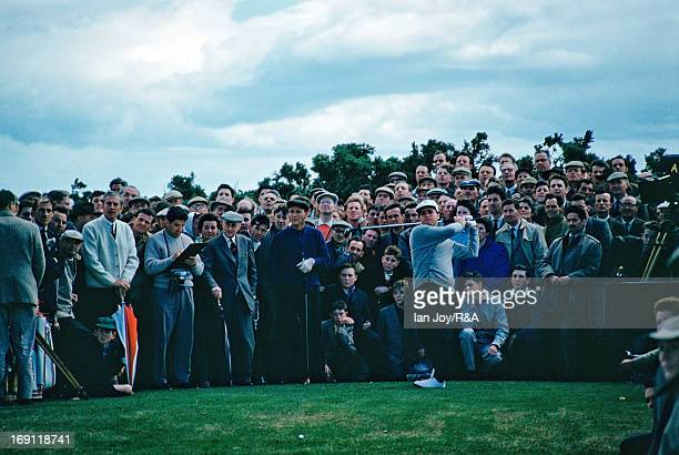 Gary Player of South Africa drives at the 14th hole watched by Arnold Palmer of the USA during the 1960 Open Championship held on the Old Course at...