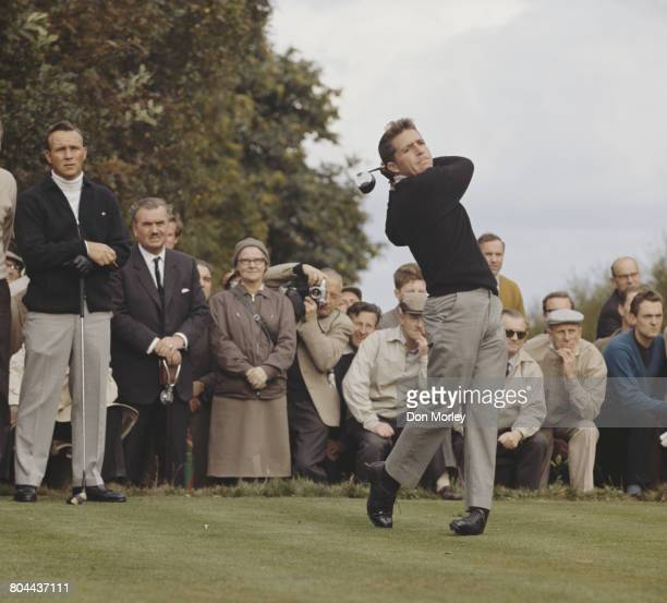 Gary Player of South Africa drives off the 4th tee as Arnold Palmer and the spectators look on during the first Piccadilly World Match Play...