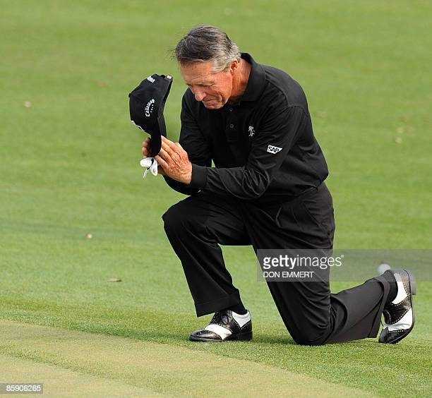 Gary Player of South Africa kneels down as he walks up to the 18th hole for his last time at the Masters during the 2nd round of the 2009 Masters at...