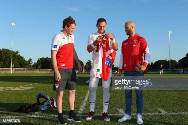 Gary Rohan and Jarrad McVeigh of the Sydney Swans present Kaeller Chryst of Stanford University with a Swans jersey during a US College Football...