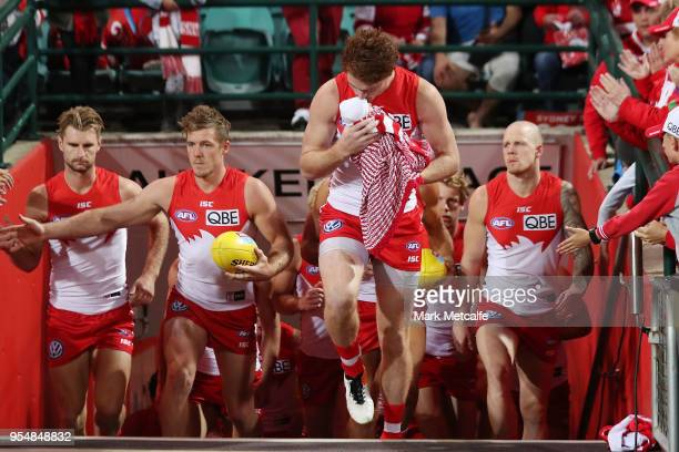 Gary Rohan of the Swans and his daughter Bella walk onto the field for his 100th match before the round seven AFL match between the Sydney Swans and...