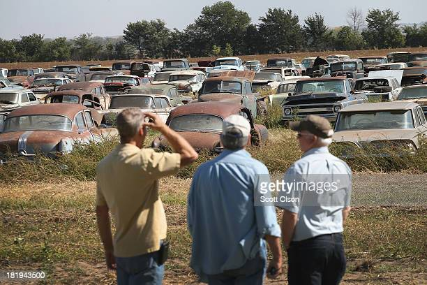 Gary Runyon from Carmel Indiana Don Miller from Cape Coral Florida and Dan Haston from Houston Texas look over classic cars lined up for auction in a...