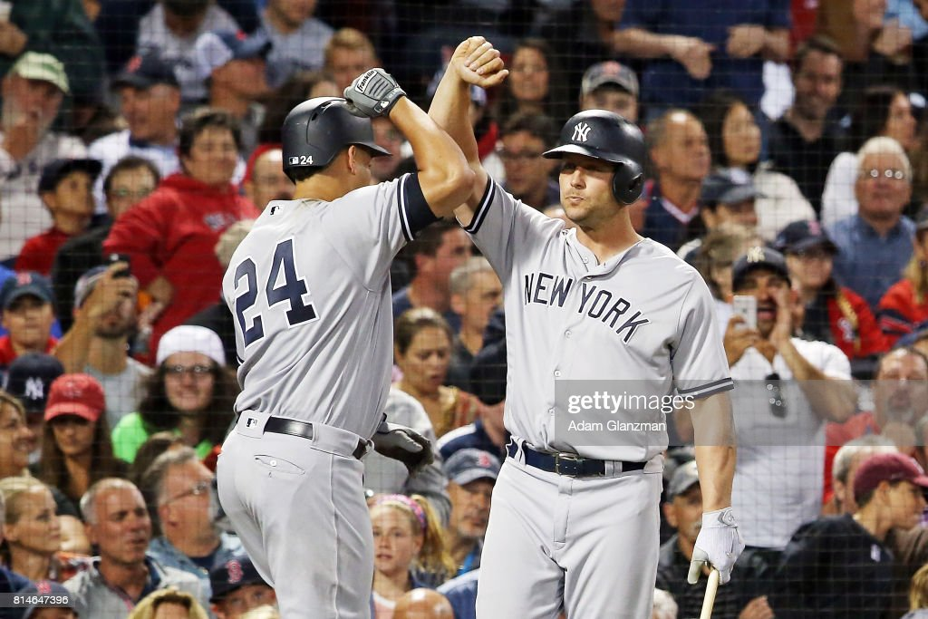 Gary Sanchez #24 high fives Matt Holiday #17 of the New York Yankees after hitting a two-run home run in the fifth inning of a game against the Boston Red Sox at Fenway Park on July 14, 2017 in Boston, Massachusetts.