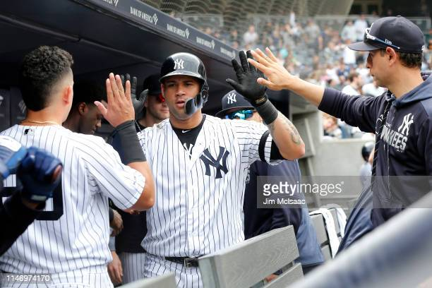 Gary Sanchez of the New York Yankees celebrates his eighth inning home run against the Minnesota Twins with his teammates in the dugout at Yankee...