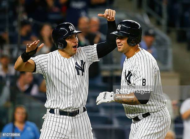 Gary Sanchez of the New York Yankees celebrates his first inning tworun home run against the Boston Red Sox with teammate Jacoby Ellsbury at Yankee...