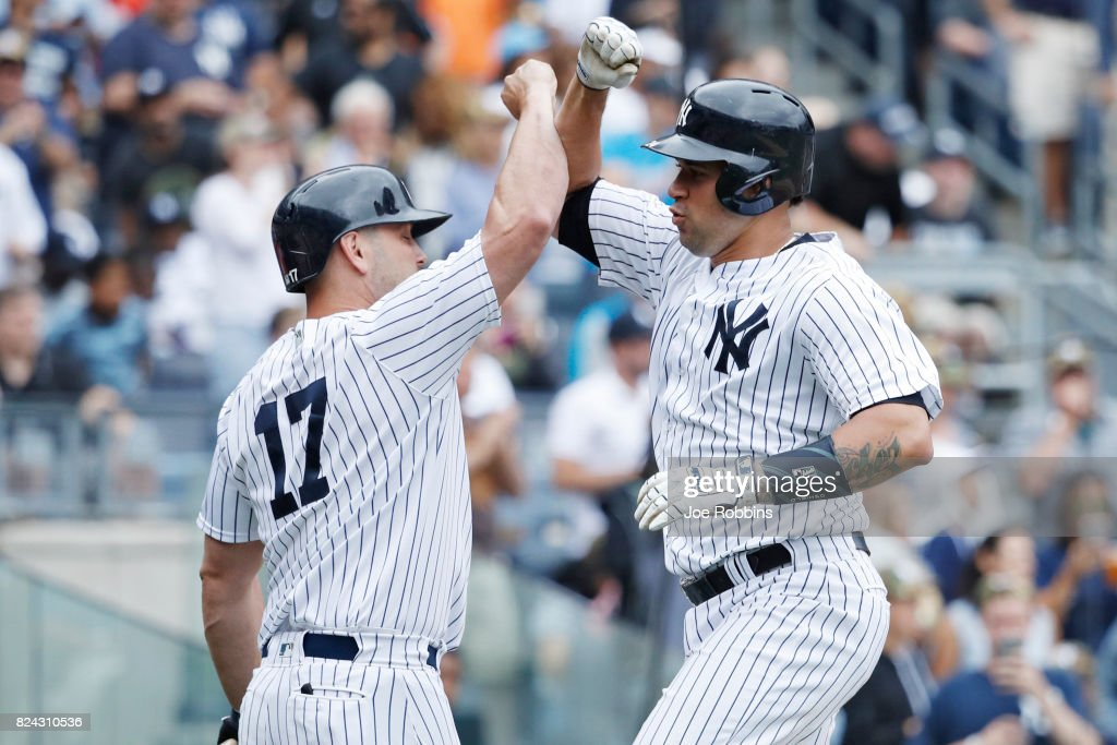 Gary Sanchez #24 of the New York Yankees celebrates with Matt Holliday #17 after a solo home run in the fourth inning of a game against the Tampa Bay Rays at Yankee Stadium on July 29, 2017 in the Bronx borough of New York City. The Yankees defeated the Rays 5-4.