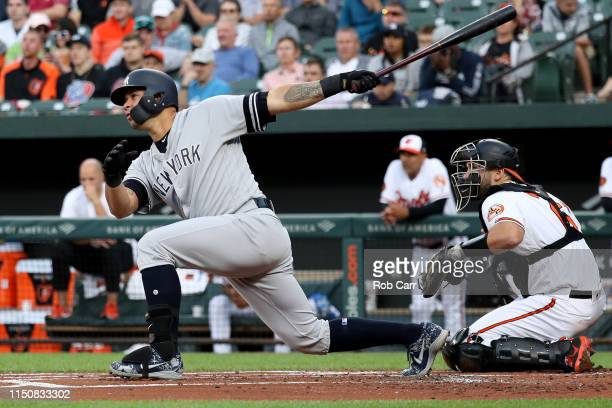 Gary Sanchez of the New York Yankees follows his three RBI home run as catcher Austin Wynns of the Baltimore Orioles looks on in the first inning at...
