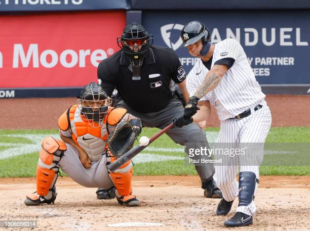 Gary Sanchez of the New York Yankees hits a long fly ball as umpire Bill Welke and catcher Pedro Severino of the Baltimore Orioles watch the ball...