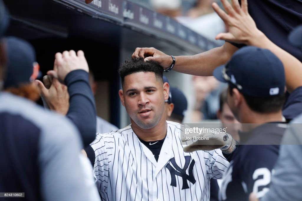 Gary Sanchez #24 of the New York Yankees is congratulated by teammates after a solo home run in the fourth inning of a game against the Tampa Bay Rays at Yankee Stadium on July 29, 2017 in the Bronx borough of New York City. The Yankees defeated the Rays 5-4.