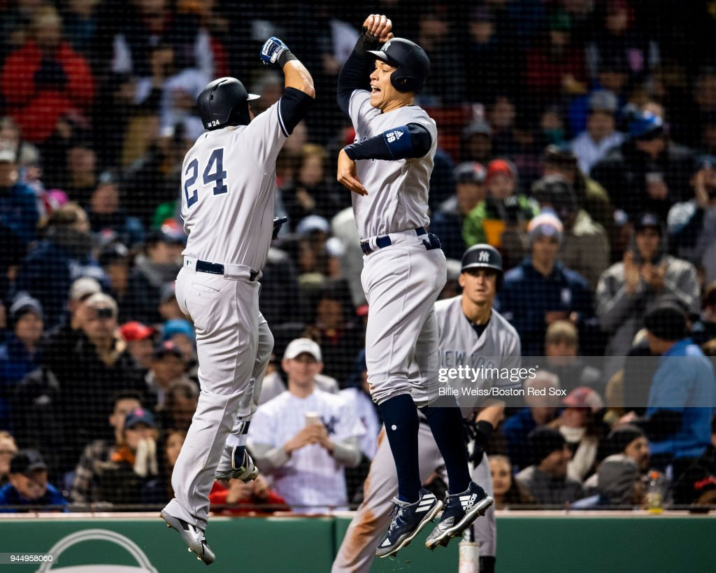 Gary Sanchez #24 of the New York Yankees reacts with Aaron Judge #99 after hitting a two run home run during the fourth inning of a game against the Boston Red Sox on April 11, 2018 at Fenway Park in Boston, Massachusetts.