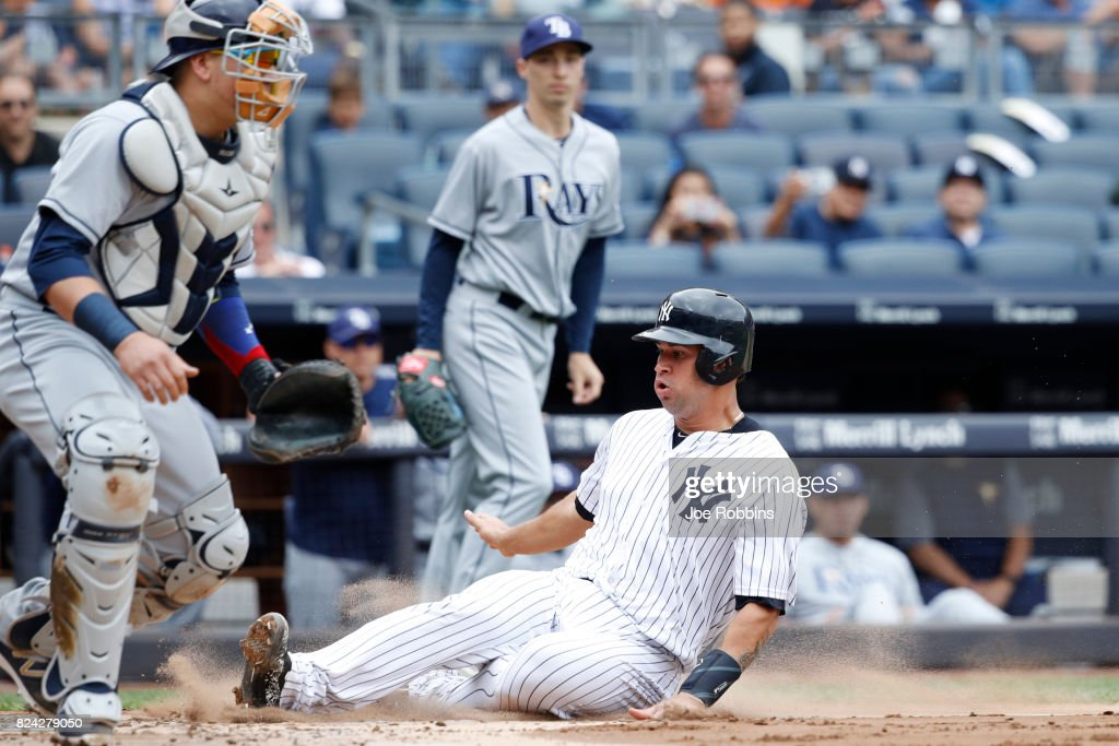 Gary Sanchez #24 of the New York Yankees slides safely at home plate after a sacrifice fly by Didi Gregorius in the second inning of a game against the Tampa Bay Rays at Yankee Stadium on July 29, 2017 in the Bronx borough of New York City.