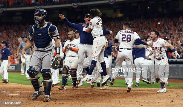 Gary Sanchez of the New York Yankees walks off the field as the Houston Astros celebrate a walkoff home run by Jose Altuve of the Houston Astros in...