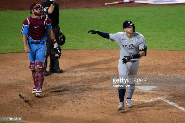 Gary Sanchez of the New York Yankees watches his two-run home run leave the park as catcher J.T. Realmuto of the Philadelphia Phillies looks on in...