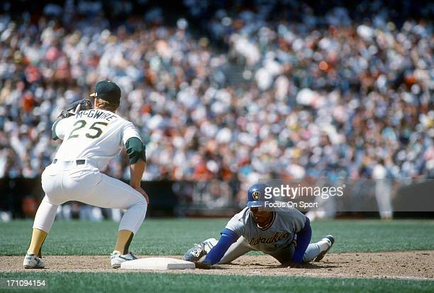 Gary Sheffield of the Milwaukee Brewers dives back into first base safe beating the throw over to Mark McGwire of the Oakland Athletics during an...