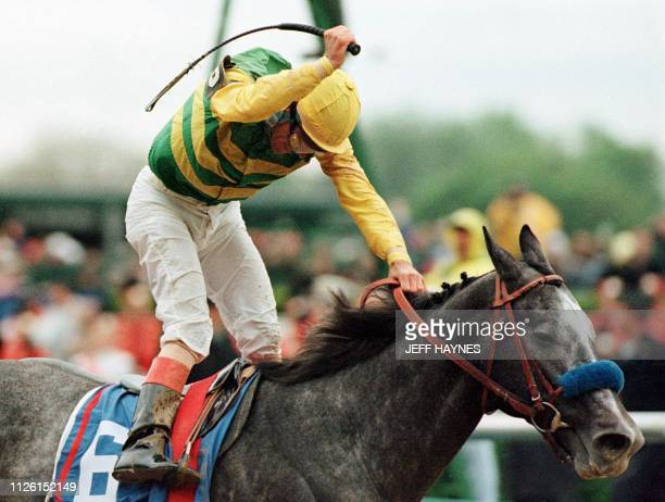 Gary Stevens raises his crop as he crosses the finish line aboard Silver Charm to win the 123rd Kentucky Derby at Churchill Downs in Louisville...