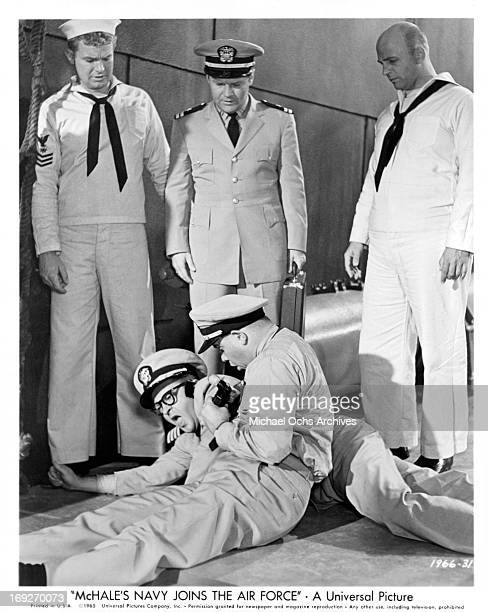 Gary Vinson, Bob Hastings, and Gavin MacLeod gather around as Tim Conway tries to take an up close picture of Joe Flynn in a scene from the film...
