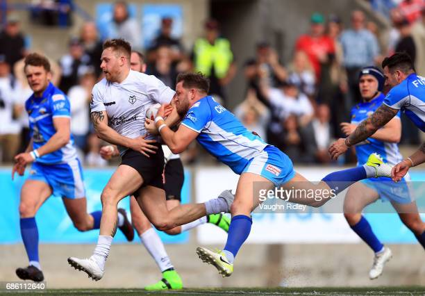 Gary Wheeler of Toronto Wolfpack is tackled by Lewis Charnock of Barrow Raiders in the first half of a Kingstone Press League 1 match at Lamport...