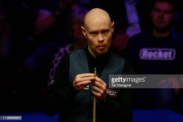 Gary Wilson of England chalks the cue in the semifinal match against Judd Trump of England on day thirteen of the 2019 Betfred World Snooker...