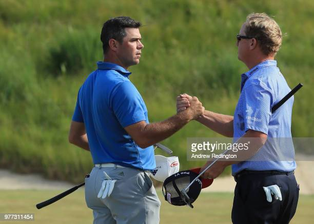 Gary Woodland of the United States and Charley Hoffman of the United States shake hands on the 18th hole during the final round of the 2018 US Open...