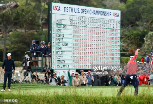 Gary Woodland of the United States celebrates on the 18th green after winning the 2019 US Open as Justin Rose of England looks on at Pebble Beach...