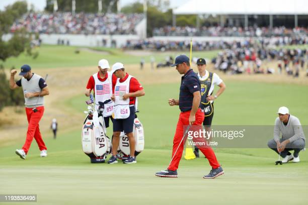 Gary Woodland of the United States team celebrates on the 12th green as Dustin Johnson of the United States team and Adam Scott of Australia and the...