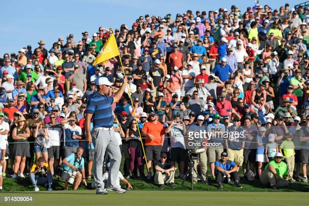 Gary Woodland pulls the flag on the 18th green during the final round of the Waste Management Phoenix Open at TPC Scottsdale on February 4 2018 in...