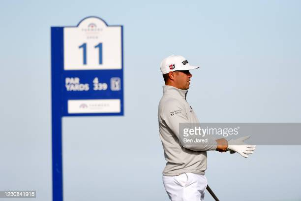 Gary Woodland puts on his glove in preparation to hit at the 11th tee on the North course during the first round of the Farmers Insurance Open at...