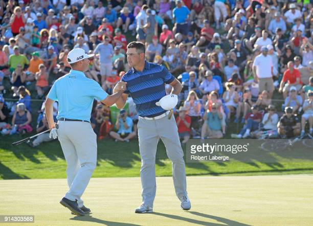 Gary Woodland shakes hands with Chez Reavie after winning in a playoff during the final round of the Waste Management Phoenix Open at TPC Scottsdale...