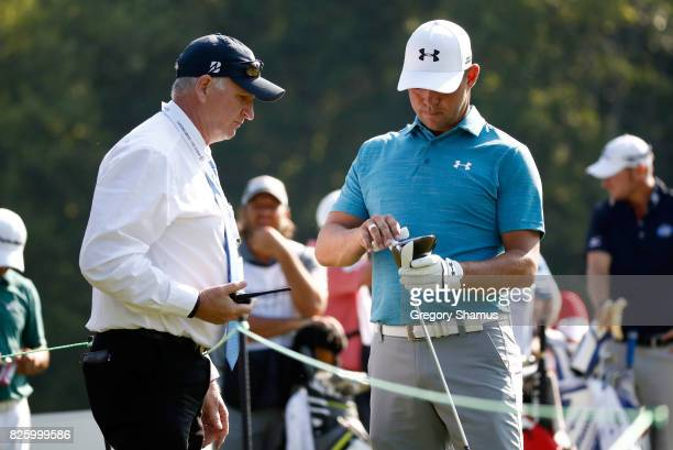Gary Woodland speaks to a rules official about tightening a screw on his driver on the sixth tee during the first round of the World Golf...