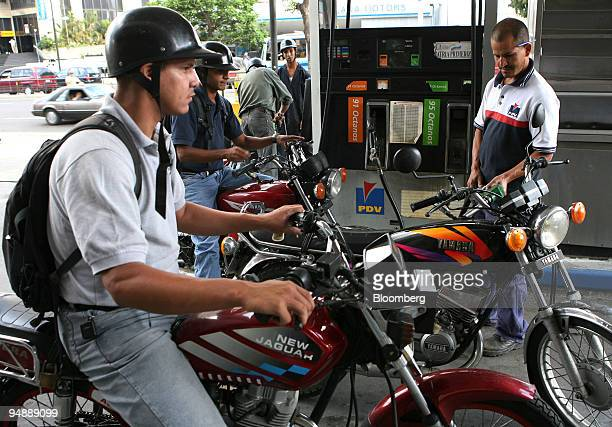 A gas attendant fills the tanks of motorcycles at a Petroleos de Venezuela SA station in Caracas Venezuela on Monday June 2 2008 PDVSA wants to ally...