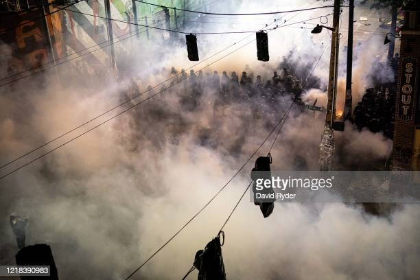 Gas fills the air as demonstrators clash with police near the Seattle Police Departments East Precinct shortly after midnight on June 8, 2020 in...