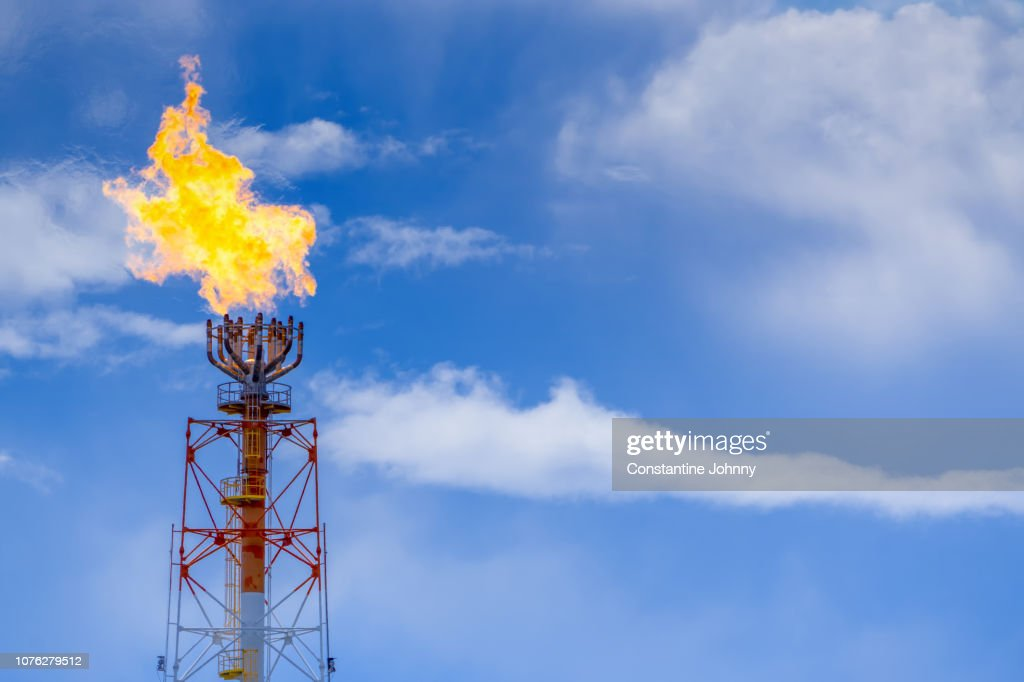 Gas Flare From a Petroleum Refinery Against Blue Sky : Stock Photo
