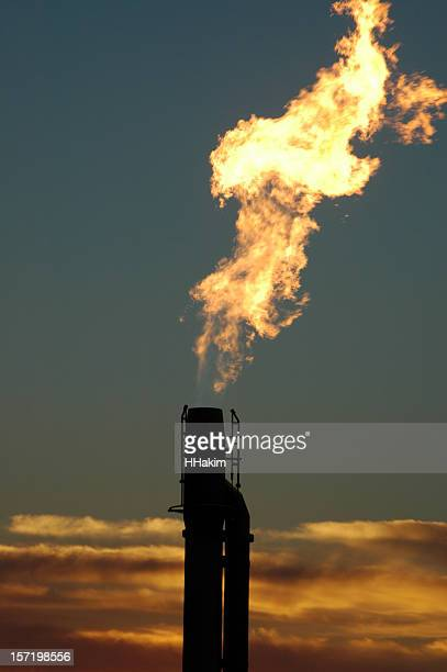 gas flare from an oil field at sunset - flare stack stock photos and pictures