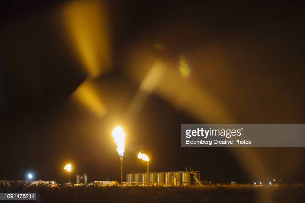 gas flares burn at a site in the permian basin - flare stack stock photos and pictures