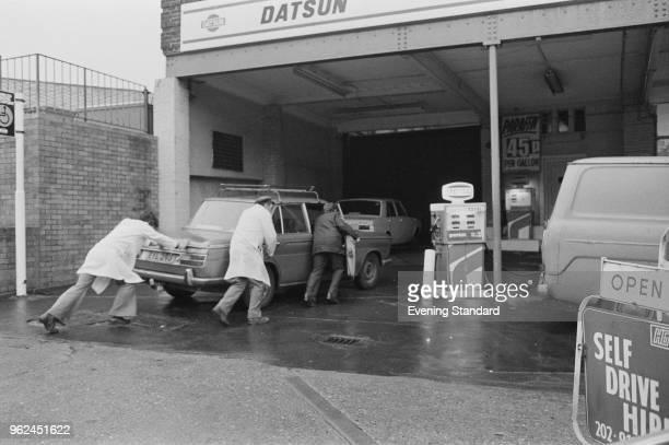 Gas jockeys helping a man to push his car near the petrol pump to refuel London UK 27th December 1978